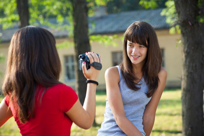 teenager girls recording with camera and posing